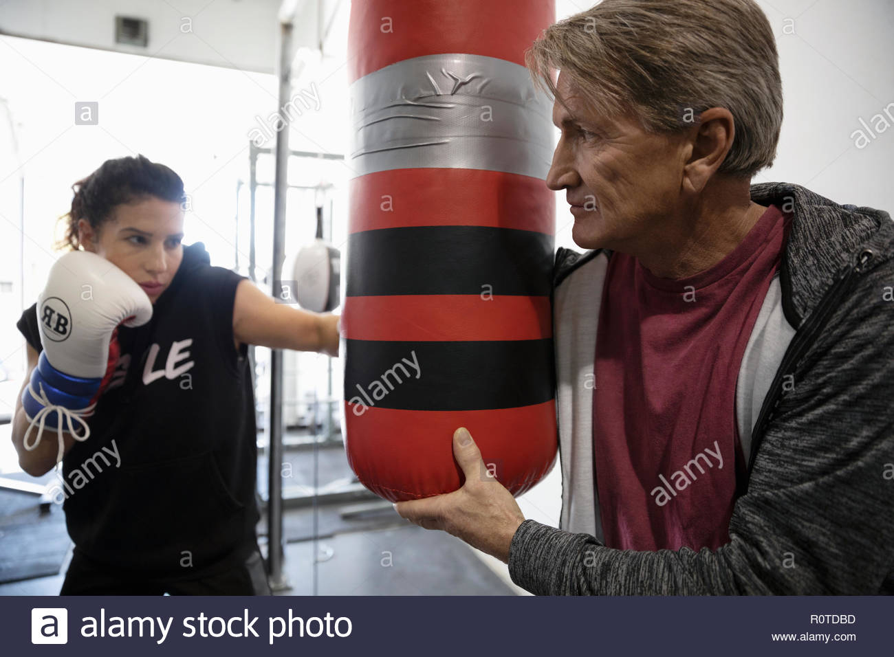 Trainer holding punching bag for female boxer training in gym - Stock Image