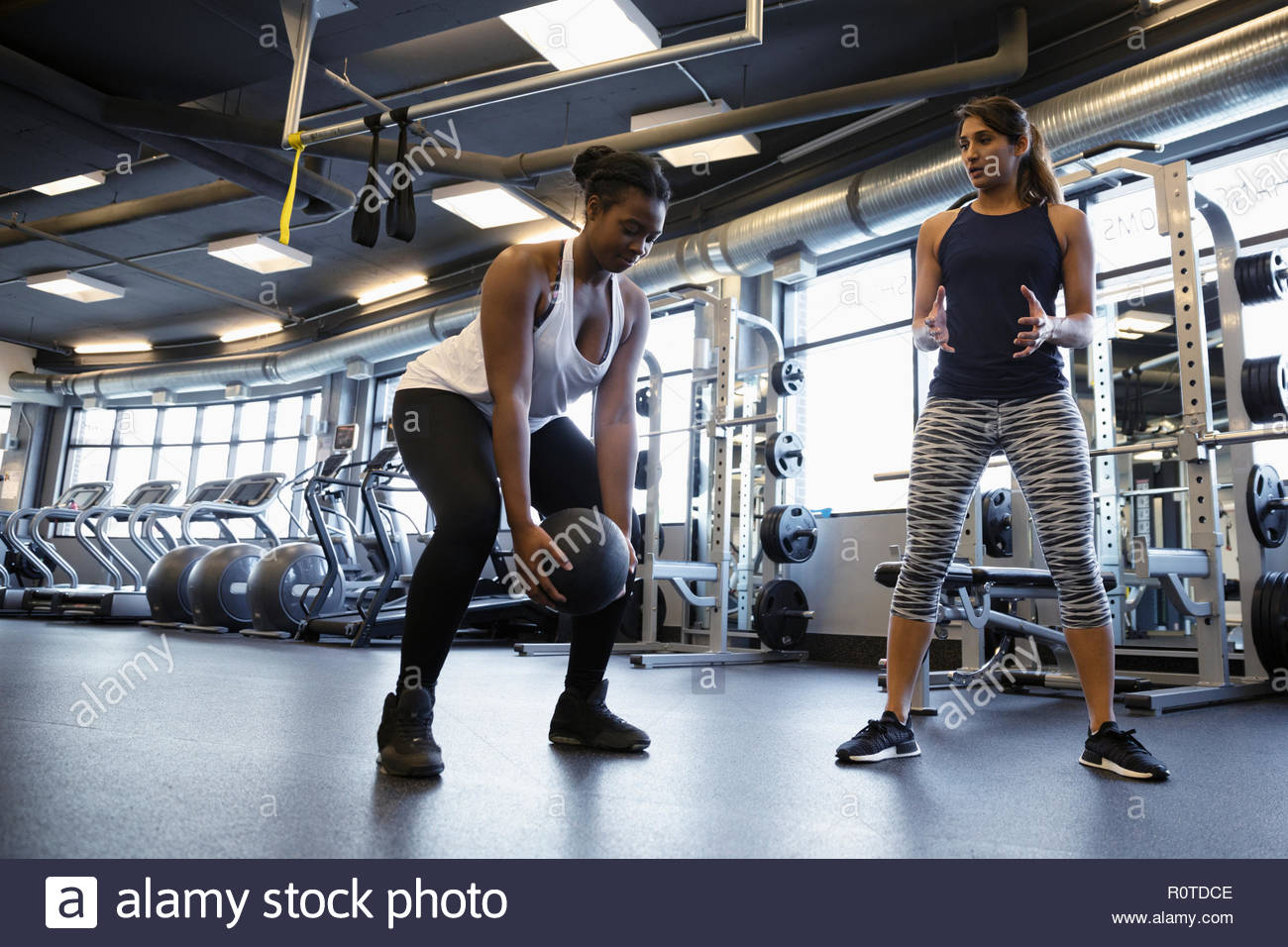 Personal trainer helping woman exercising with medicine ball in gym - Stock Image