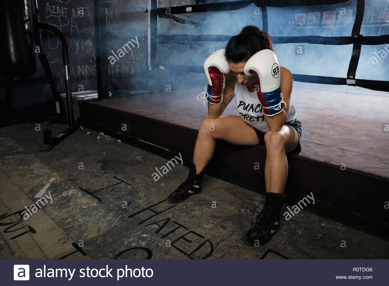 Tired female boxer resting in gym - Stock Image