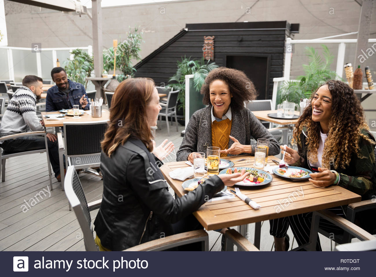 Women friends enjoying lunch on cafe patio Stock Photo