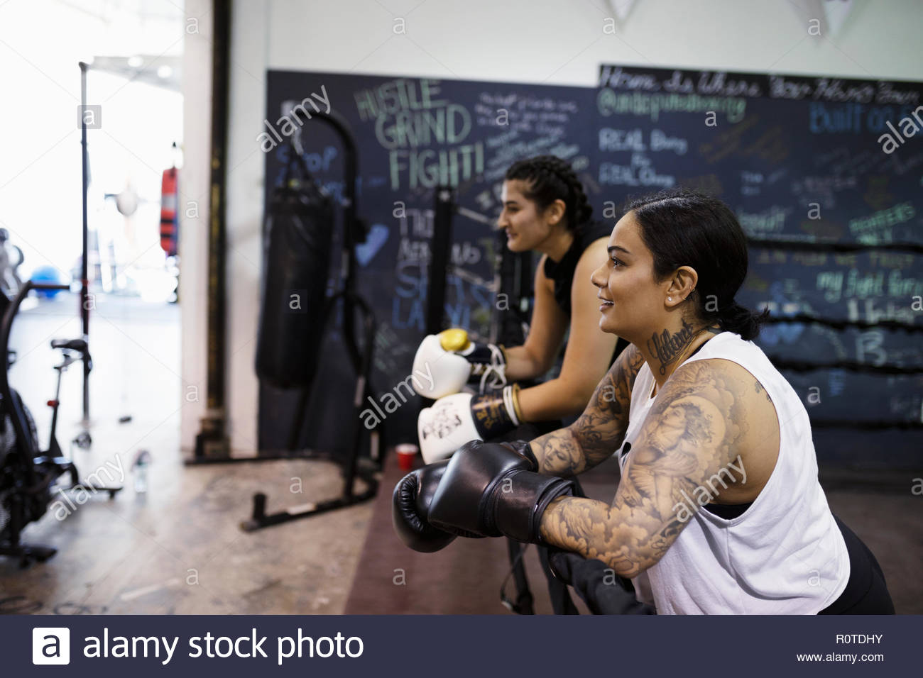 Female boxer with tattoos resting in gym - Stock Image