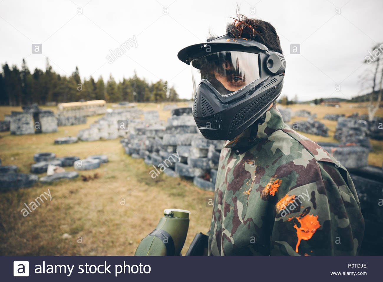Young man paintballing - Stock Image
