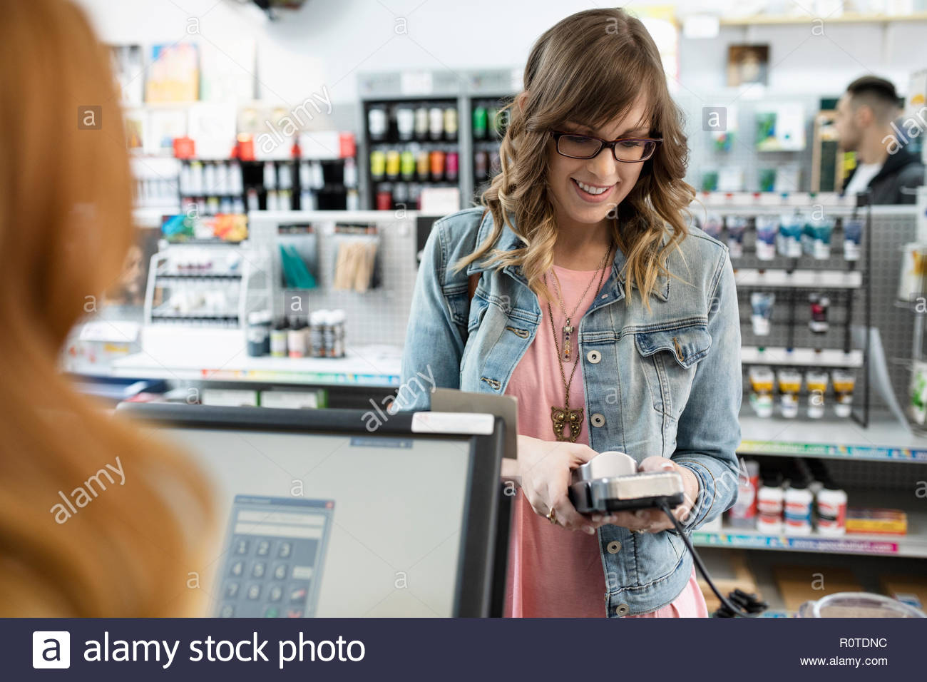 Smiling female shopper using credit card reader pin entry in art supply shop - Stock Image