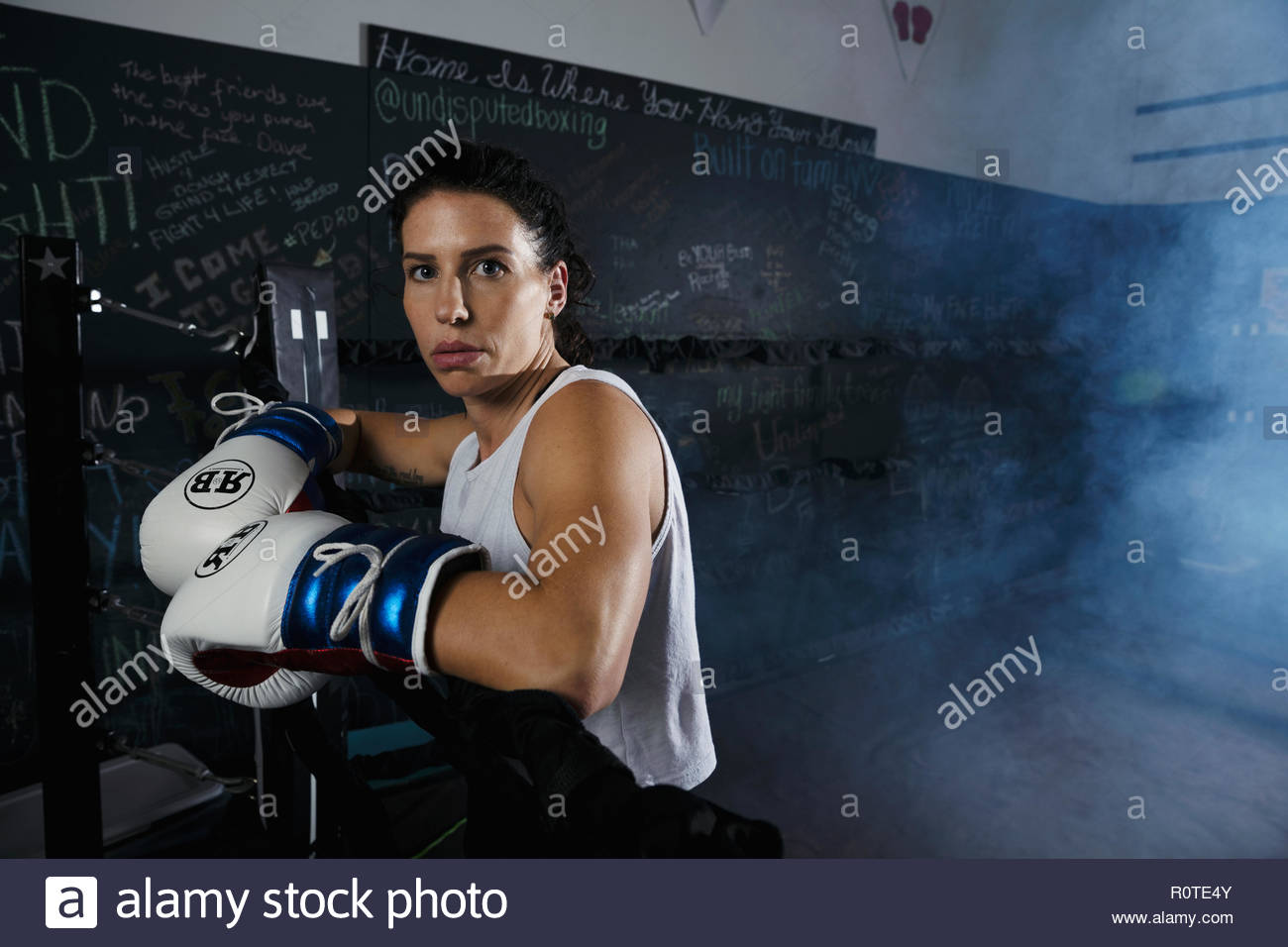 Portrait tough female boxer standing in boxing ring - Stock Image