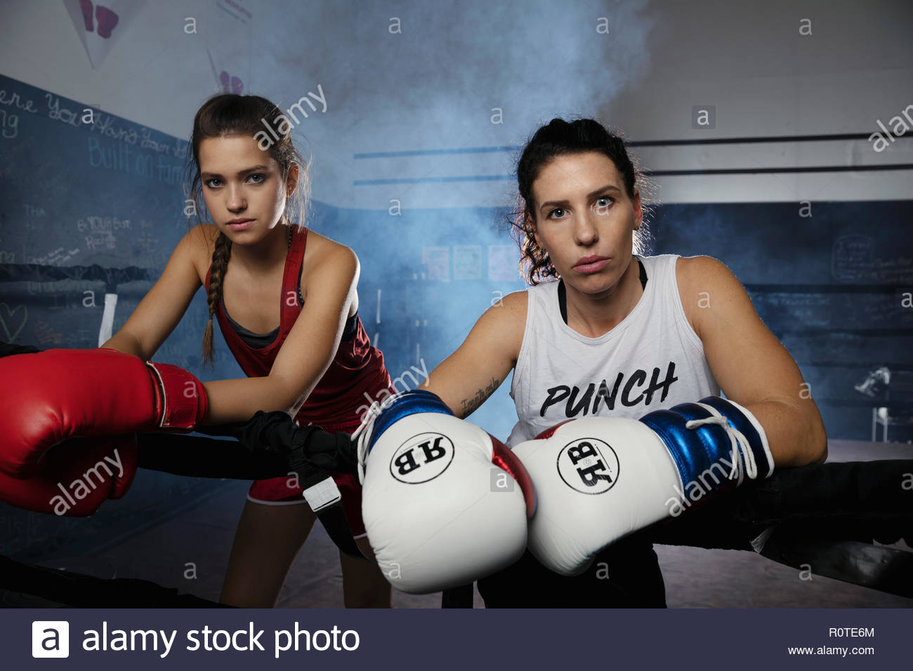 Portrait tough female boxers in boxing ring - Stock Image