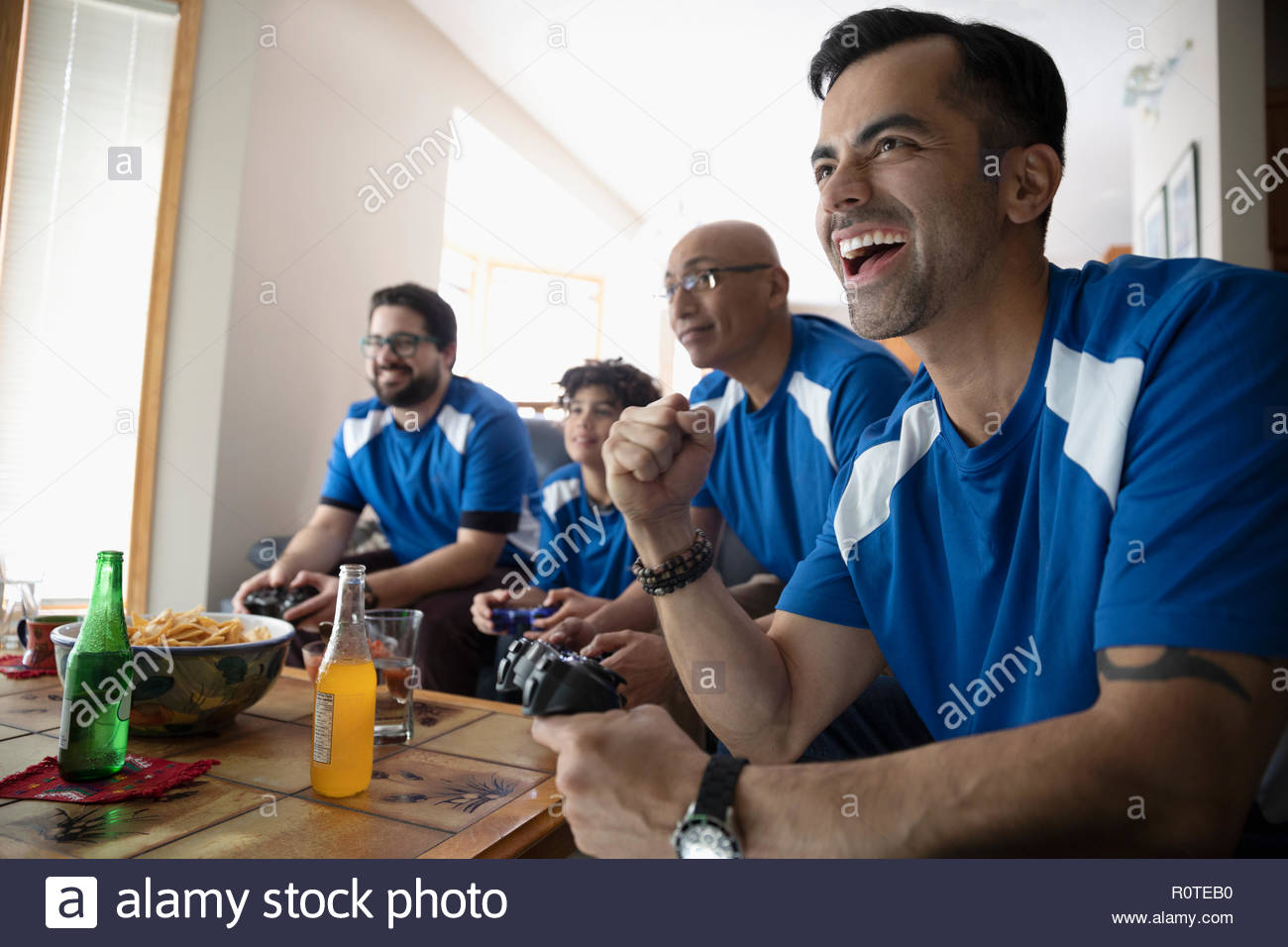 Enthusiastic Latinx multi-generation family playing sports video game - Stock Image