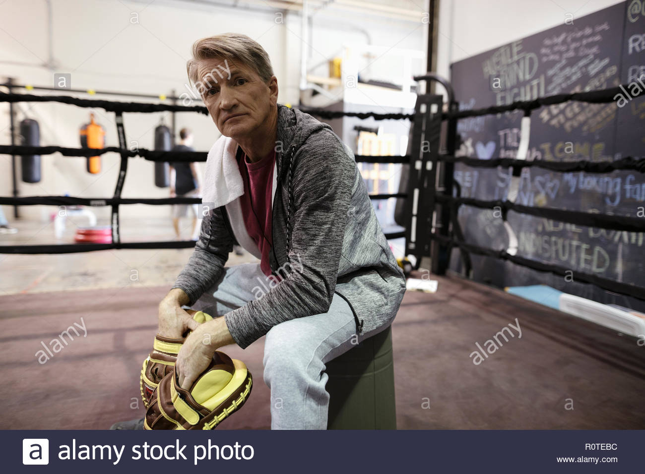 Portrait confident, tough male trainer sitting in boxing ring in gym - Stock Image