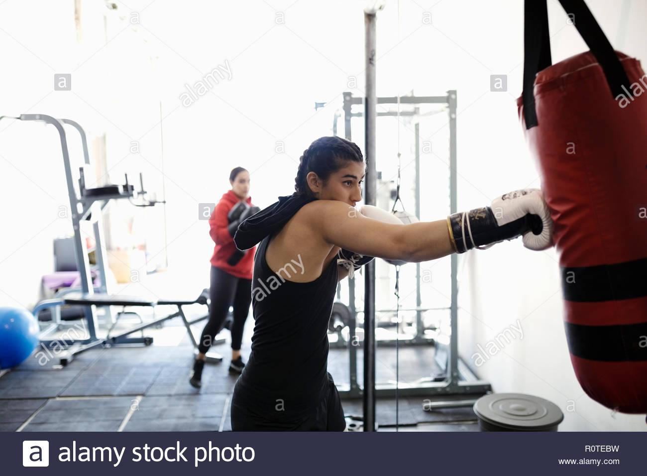 Tough female boxer training at punching bag in gym - Stock Image
