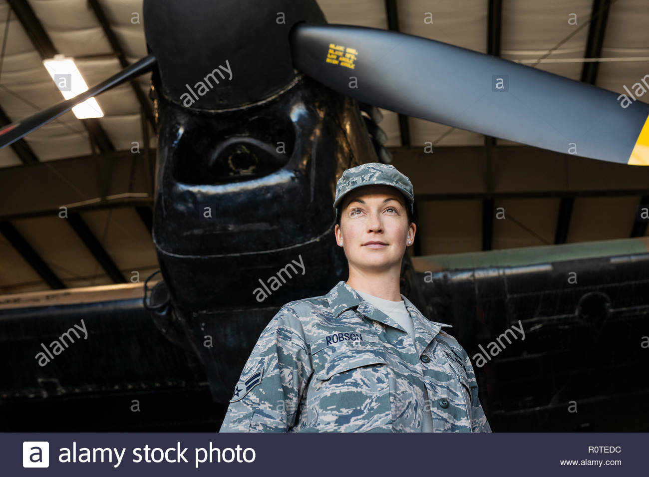 Portrait confident female army pilot standing below airplane in airplane hangar - Stock Image
