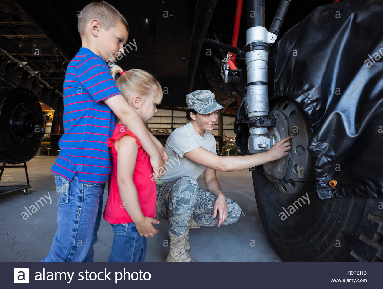 Female army engineer showing airplane landing gear to curious children - Stock Image