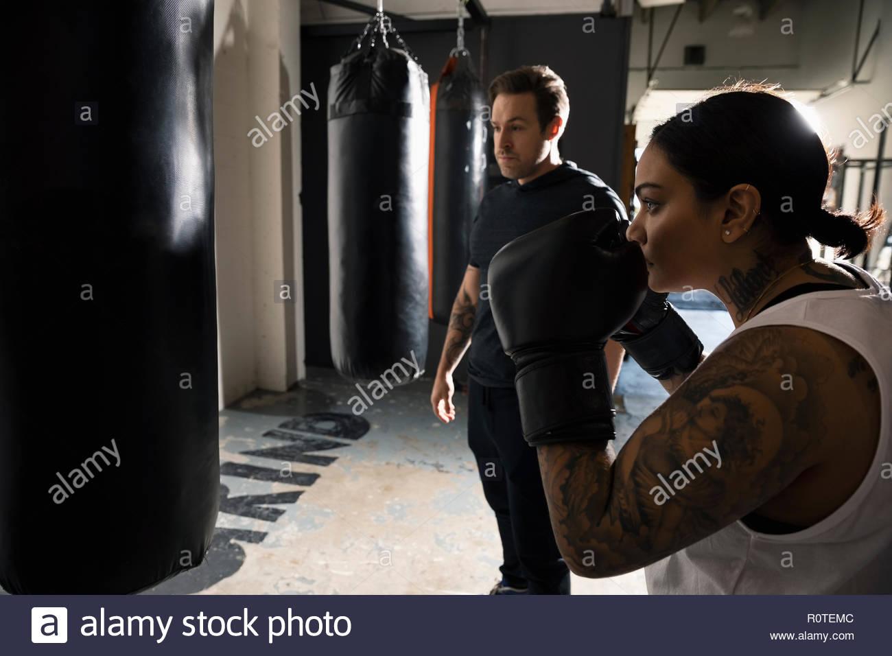 Female boxer training, boxing at punching bag in gym - Stock Image