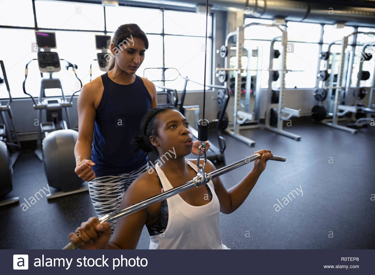 Personal trainer helping woman using exercise equipment in gym - Stock Image