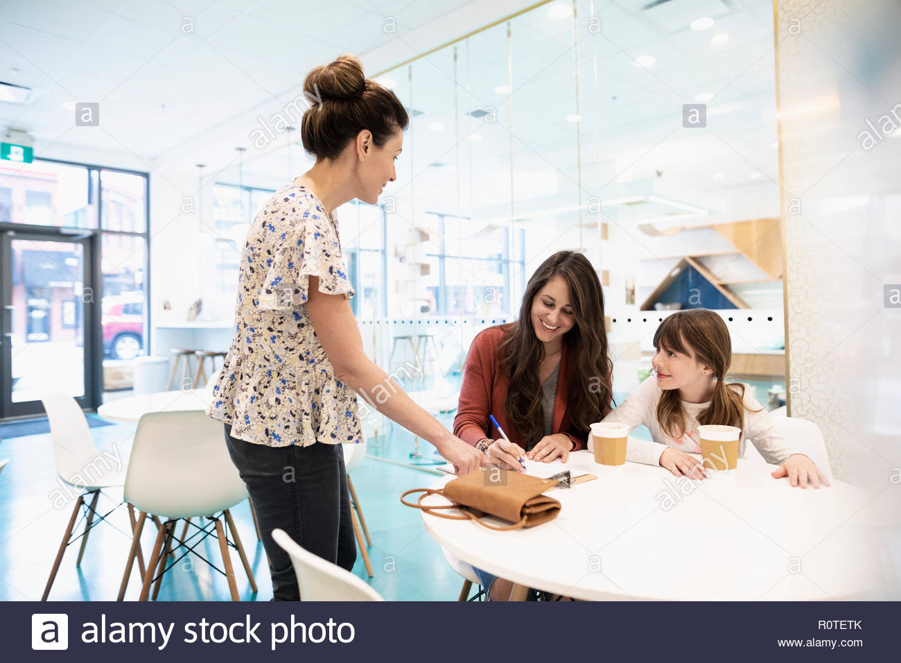 Mother and daughter drinking coffee and filling out adoption application in cat cafe - Stock Image