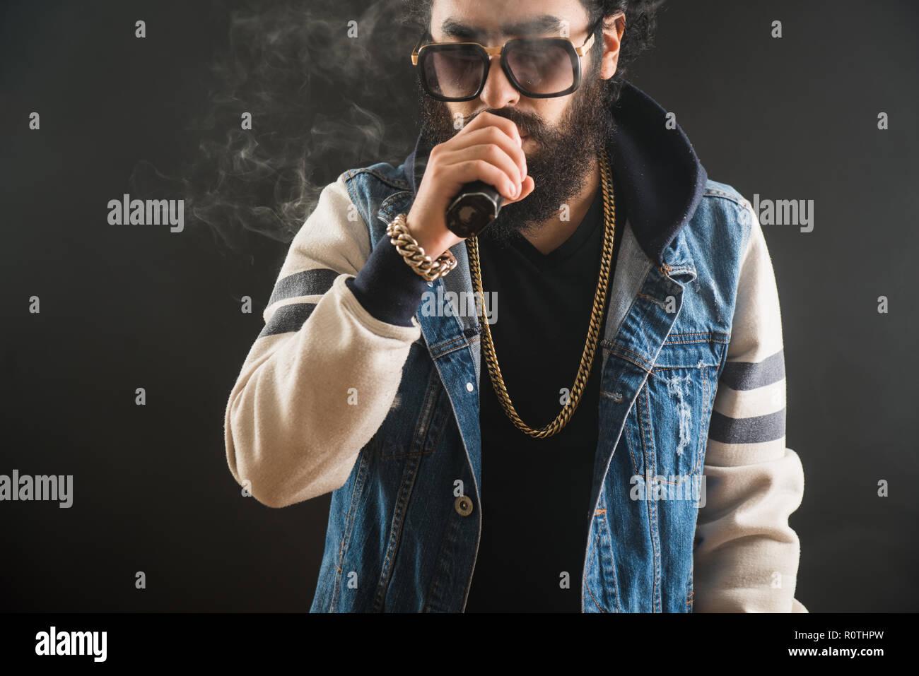Young man with beard and sunglasses vaping an electronic cigarette. Vaper hipster smoke vaporizer - Stock Image