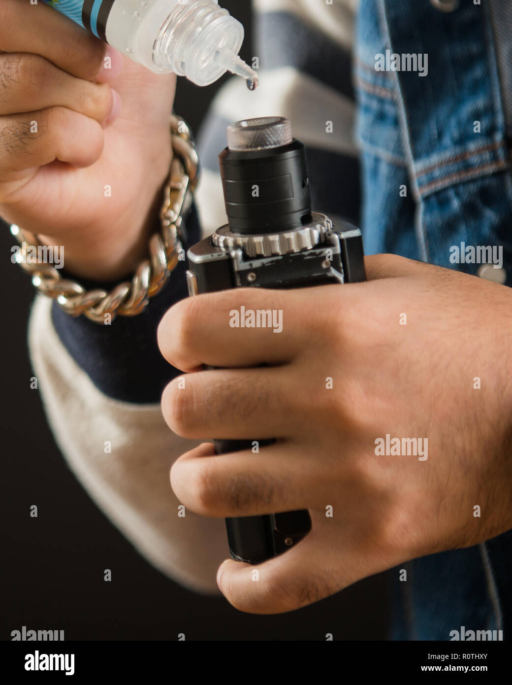 Man dripping his vape device, RDA or e-cigarette, close up, selective focus - Stock Image