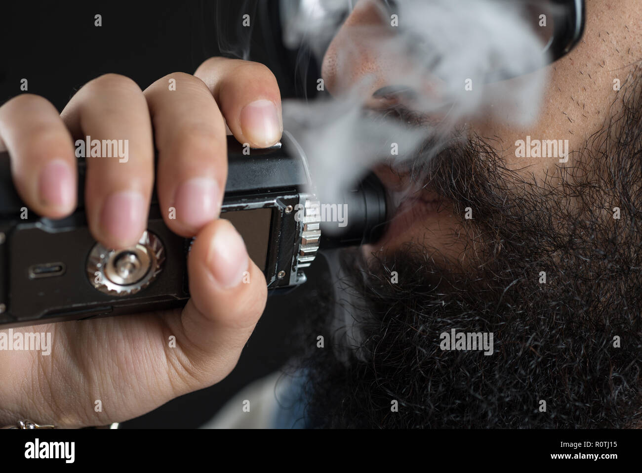 Close up of an unrecognizable young man smoking from a vape pen or vaporizer - Stock Image
