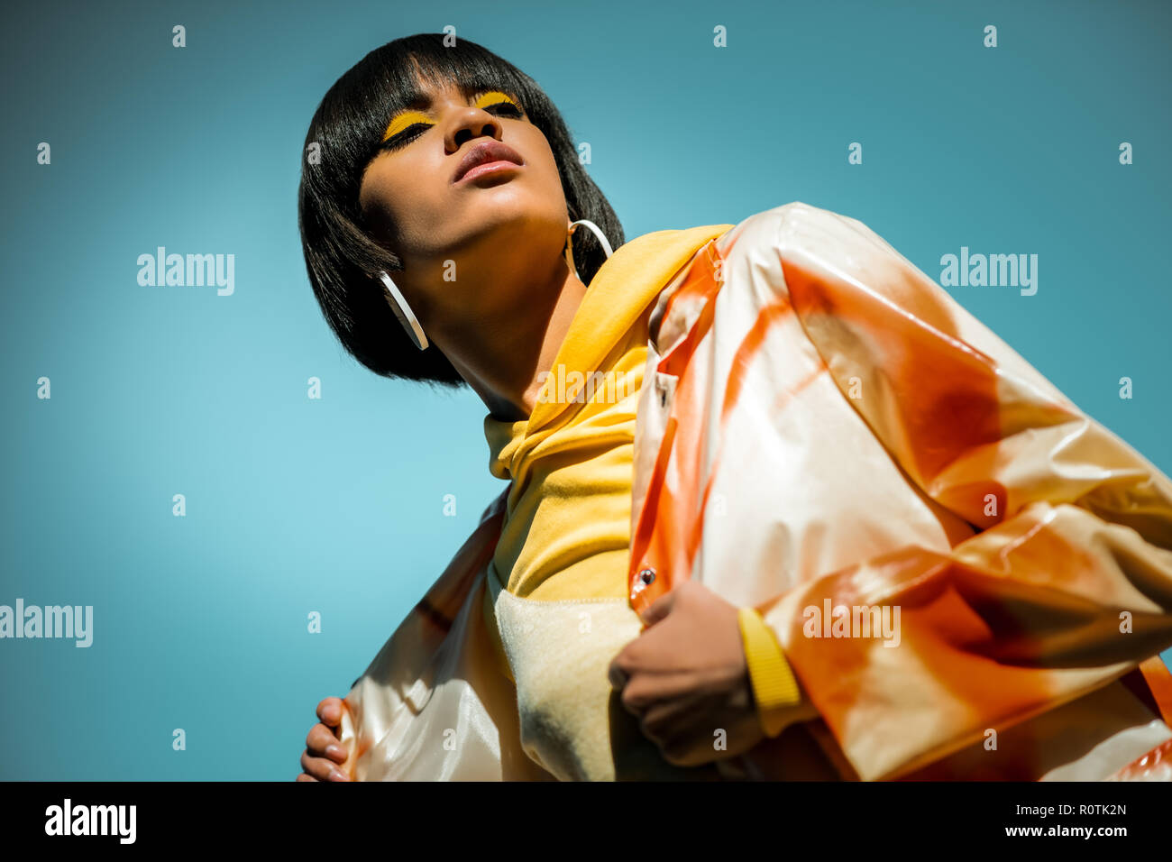 Unusual short-haired woman wearing bright orange poncho - Stock Image