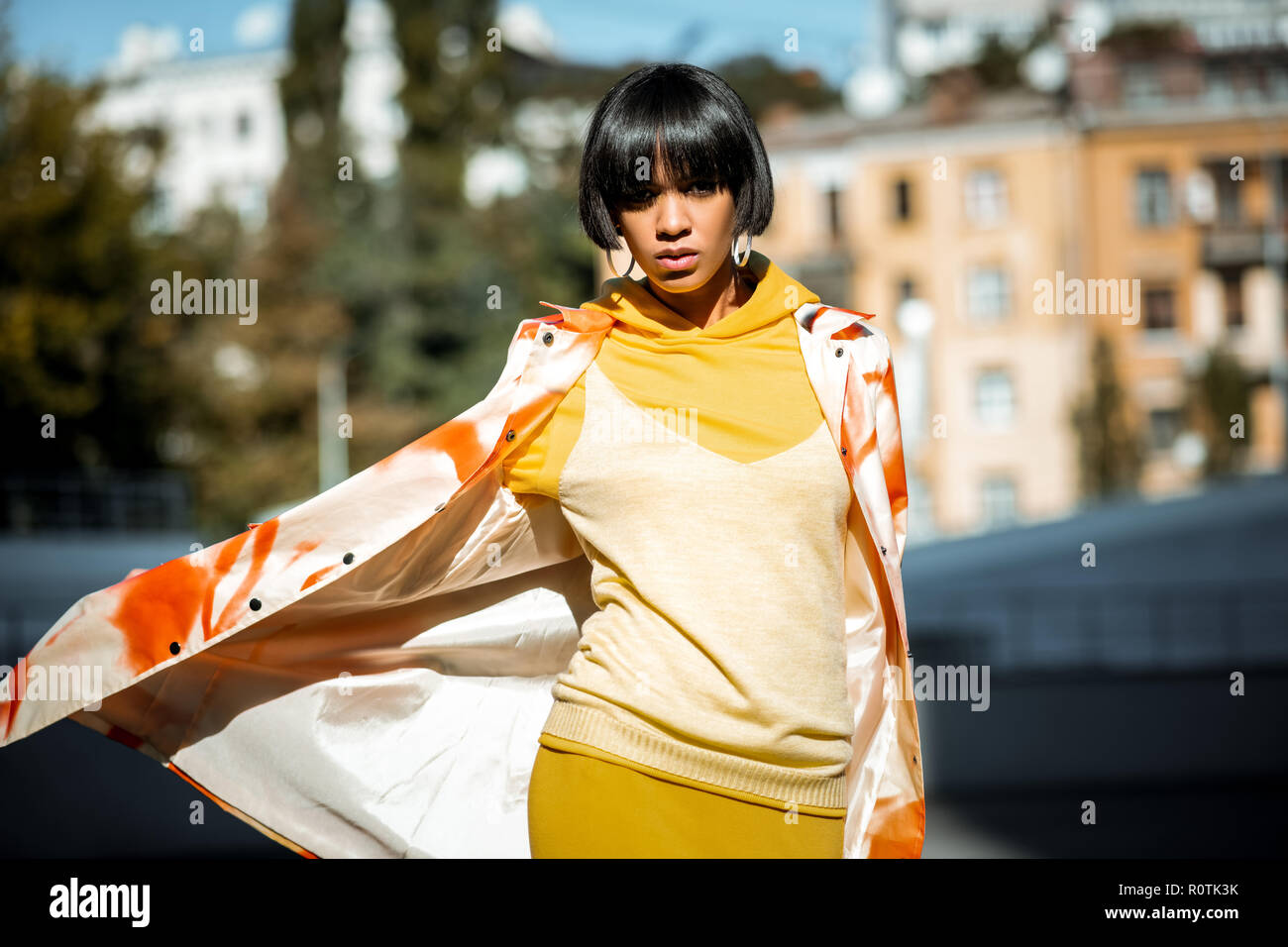 Serious young brown girl opening her cloak - Stock Image