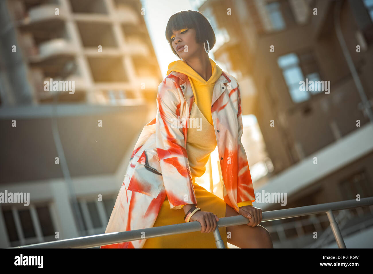 Vicious well-dressed model stooping over handrail exhibiting outfit - Stock Image