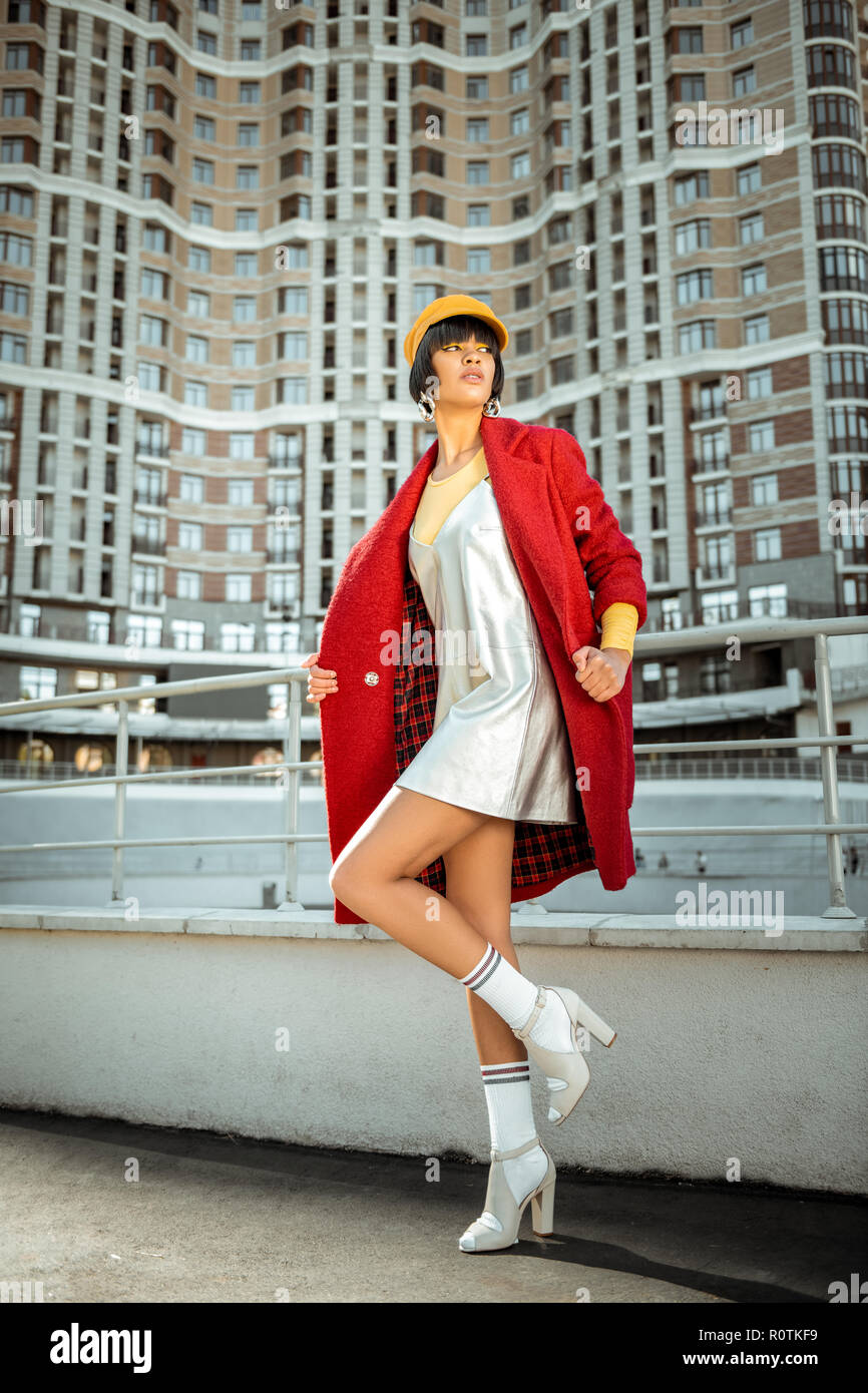 Authentic fashionable girlfriend actively posturing using buildings - Stock Image
