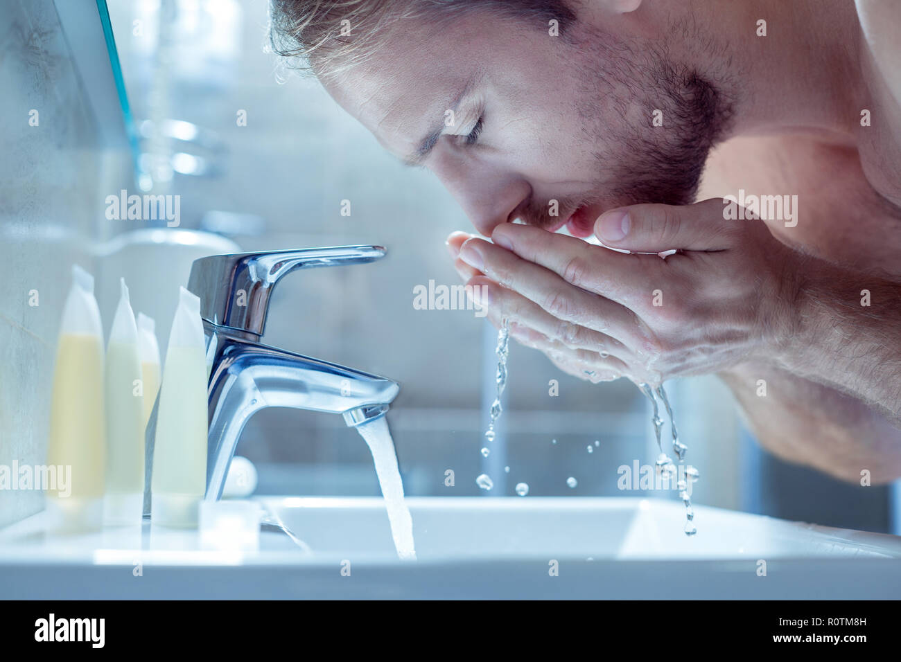 Bearded handsome man washing his face in the morning in light bathroom Stock Photo