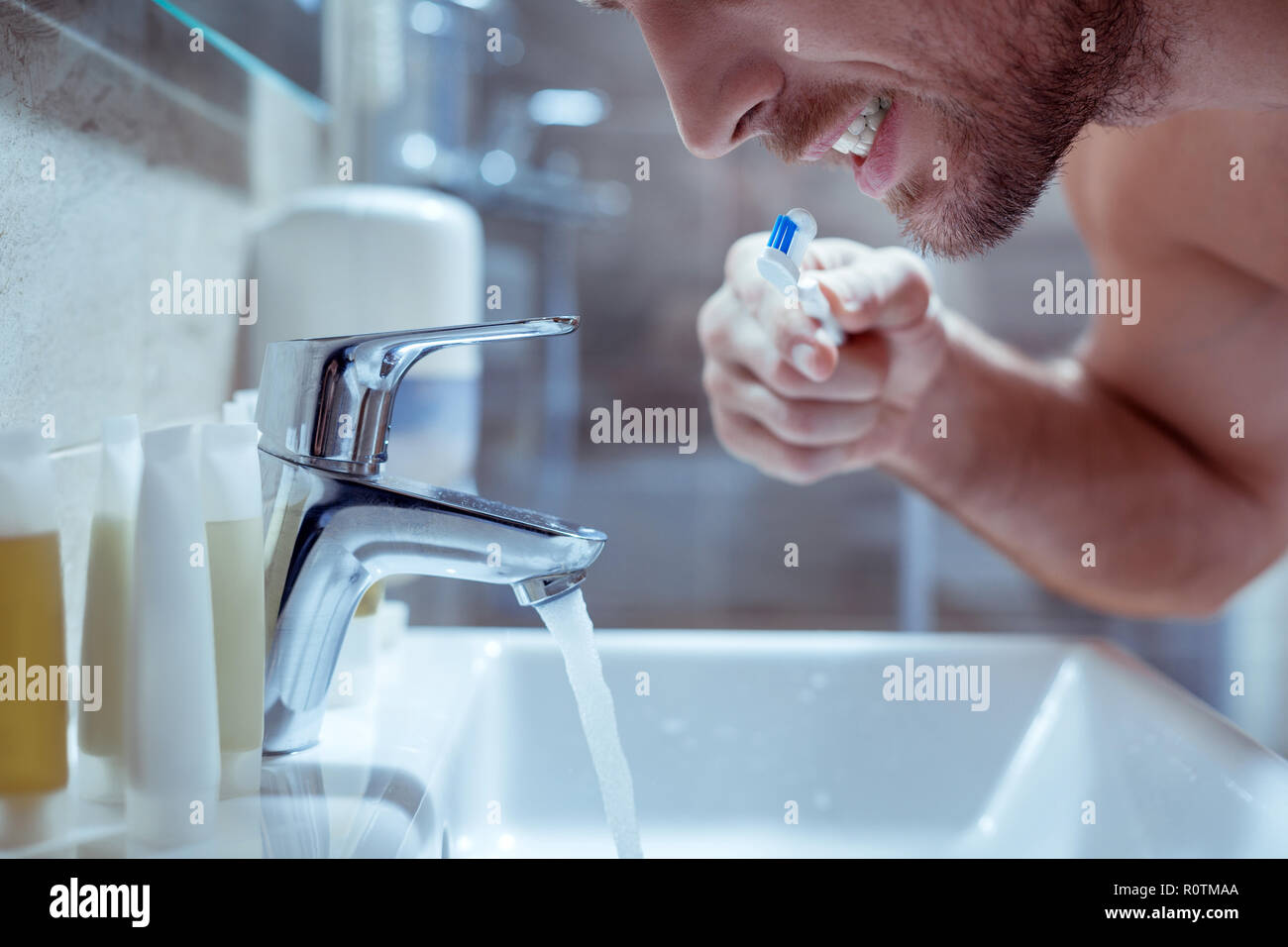 Young handsome bearded man brushing his teeth before going to bed Stock Photo