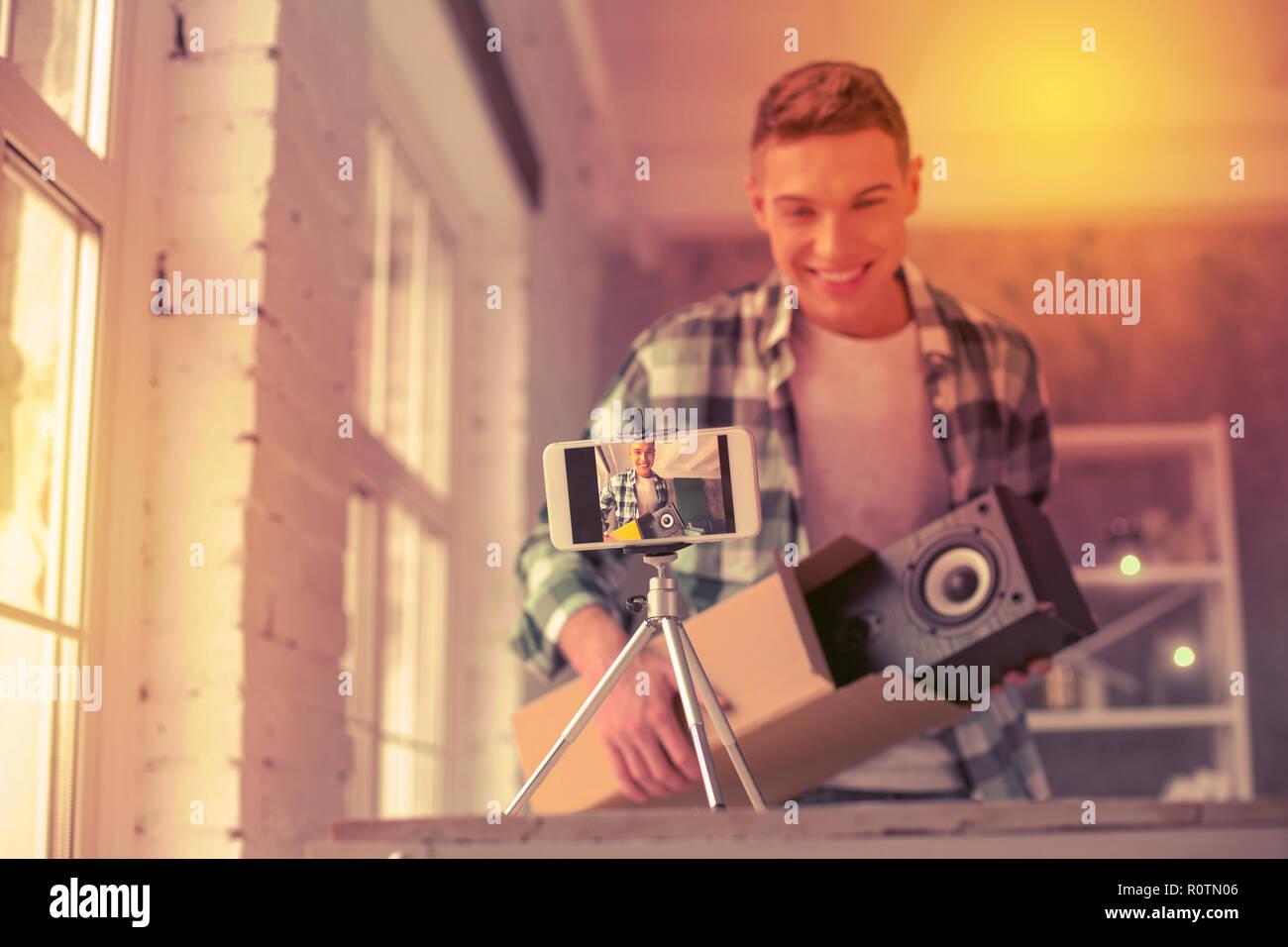 Joyful young blogger showing item hes opening - Stock Image