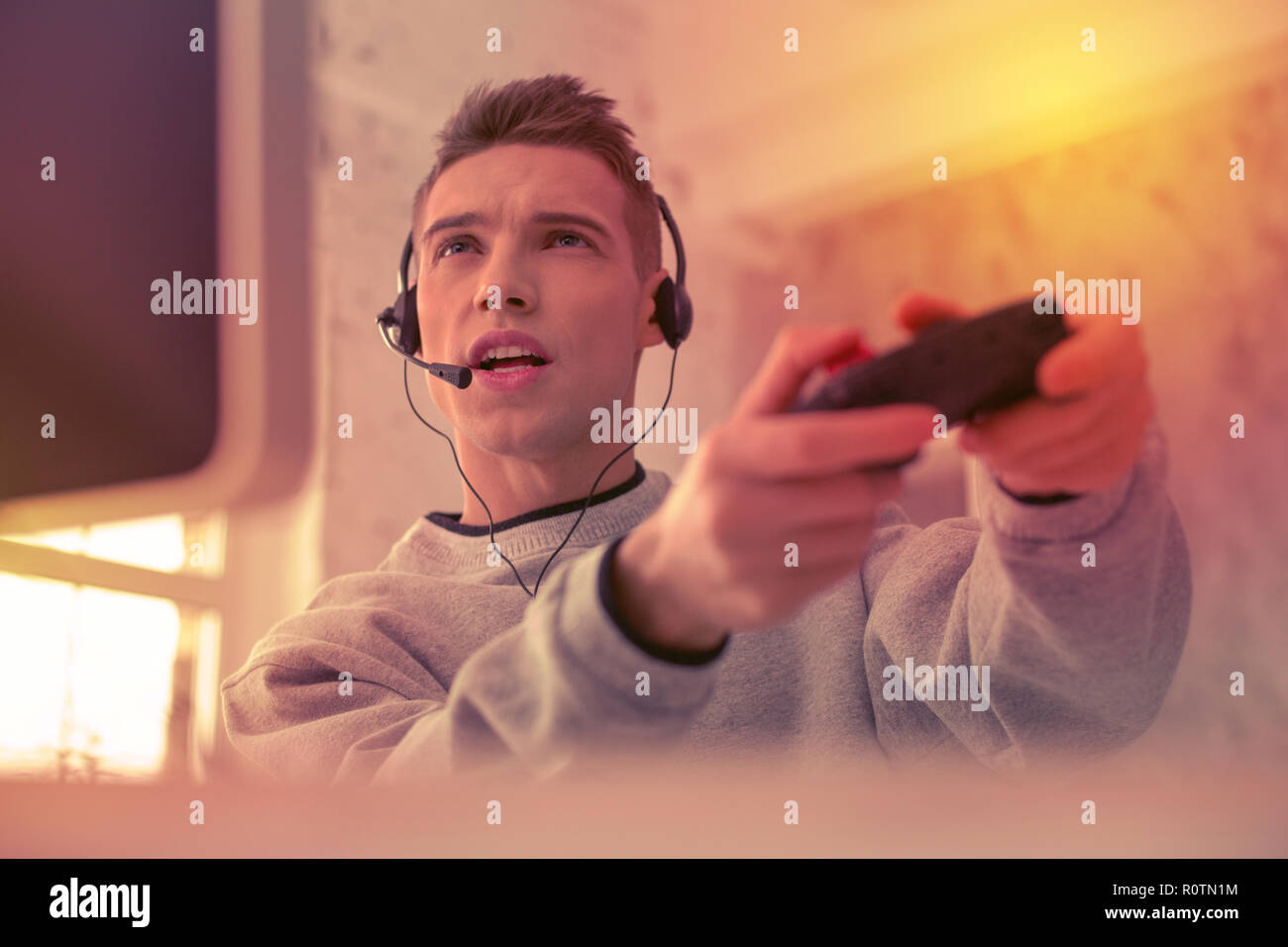 Young concentrated man enthusiastically playing with computer - Stock Image