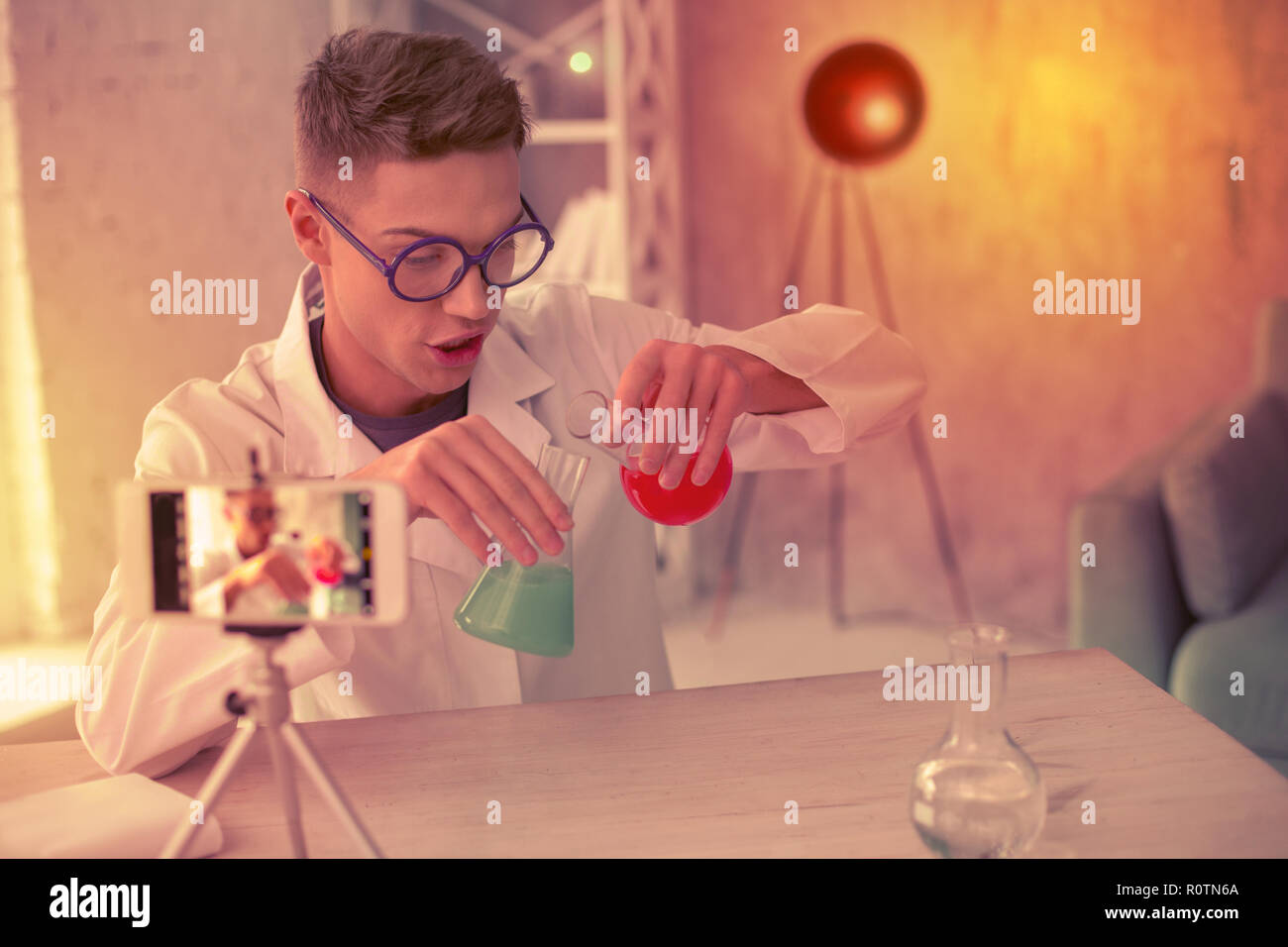 Curious scientist organizing chemistry experimentation at home - Stock Image