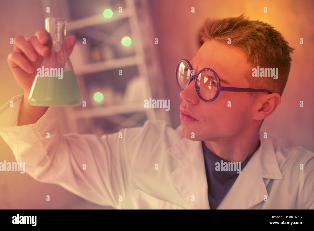 Short haired man puzzled looking on the test tube - Stock Image