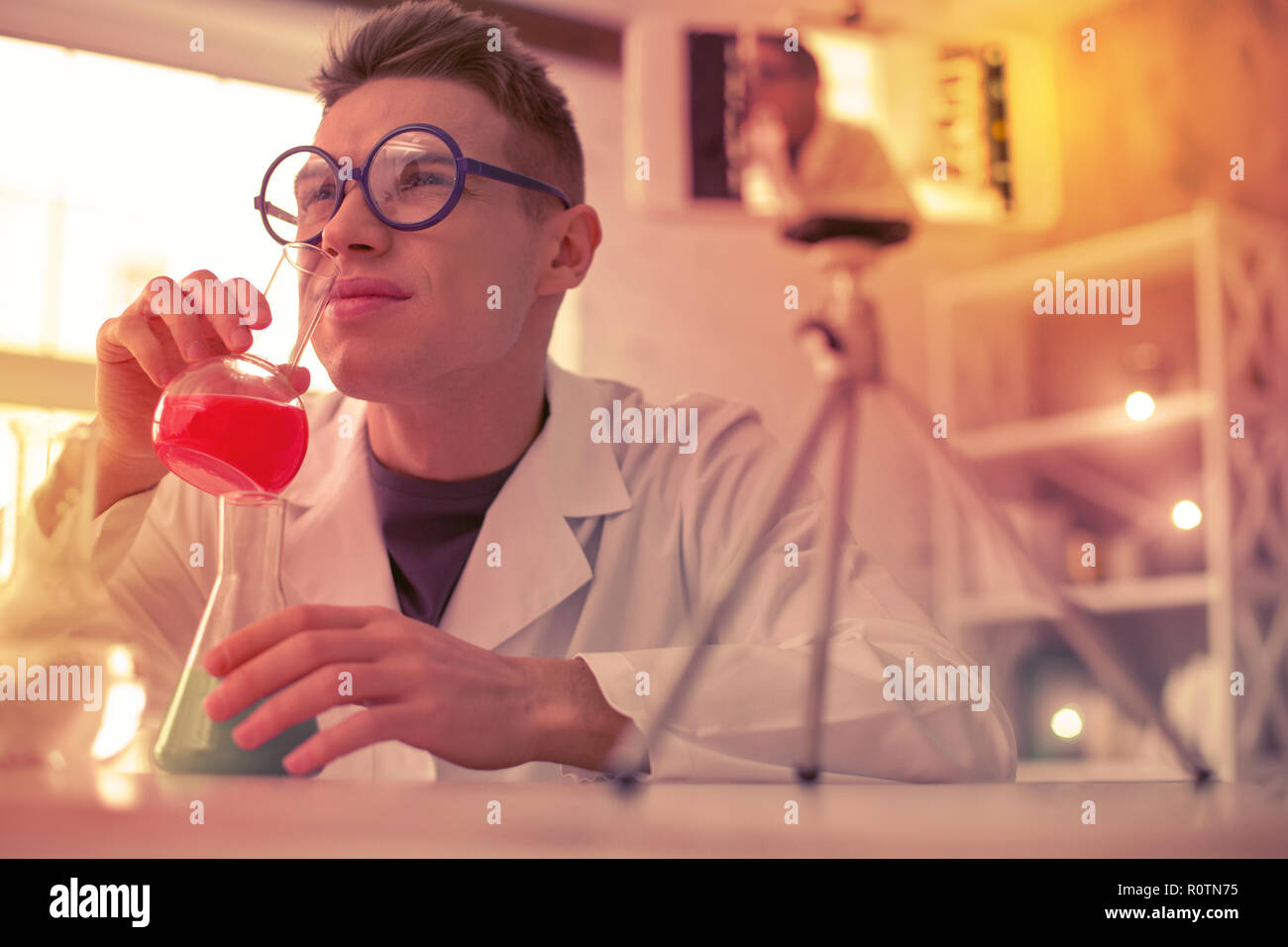 Blond puzzled man smelling unpleasant red reagent - Stock Image