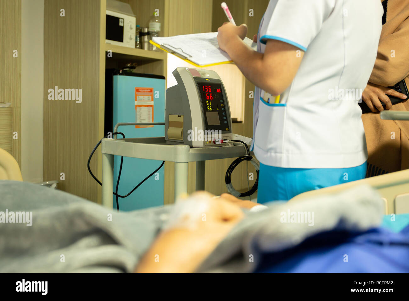 Nurse checking blood pressure on monitor screen for patient health in hospital. - Stock Image