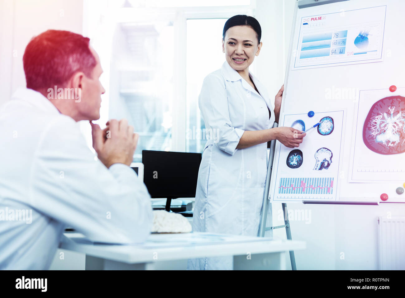 Positive smart woman pointing at the brain image - Stock Image