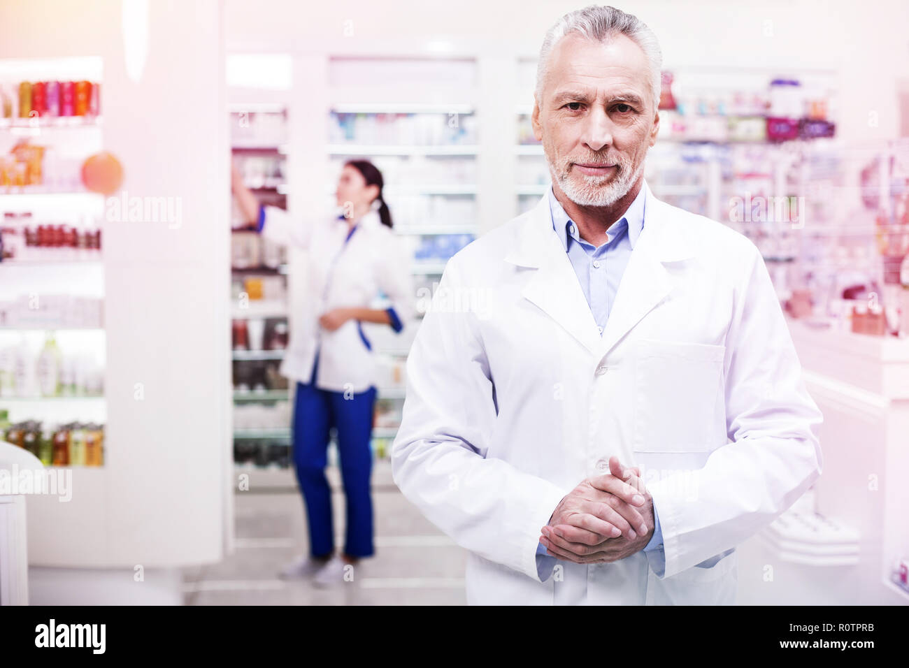 Serious gray-haired scientist in a uniform folding his arms - Stock Image