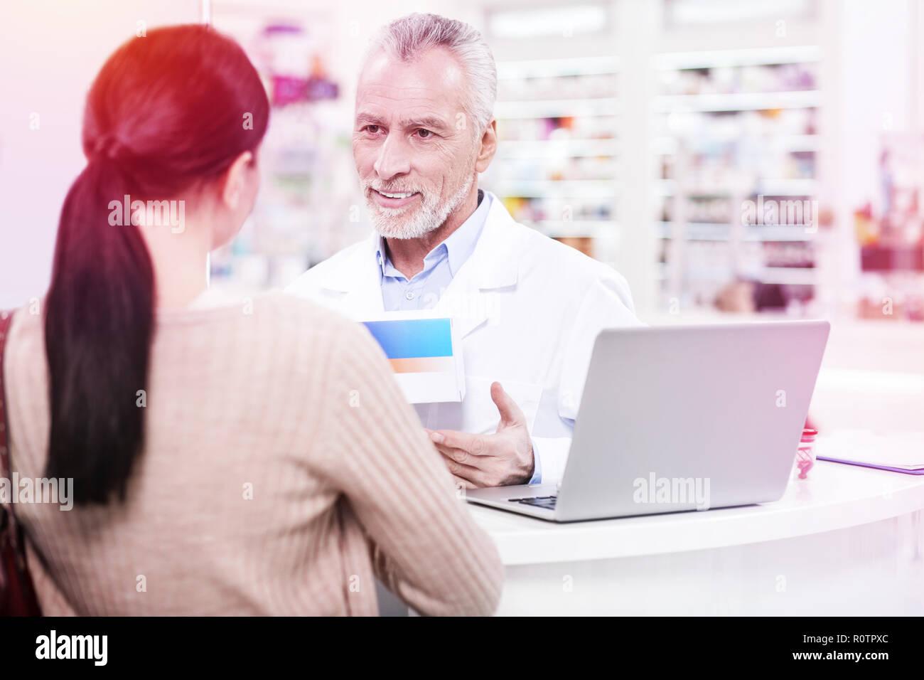 Positive senior pharmacist explaining an effect of prescription to a consumer - Stock Image