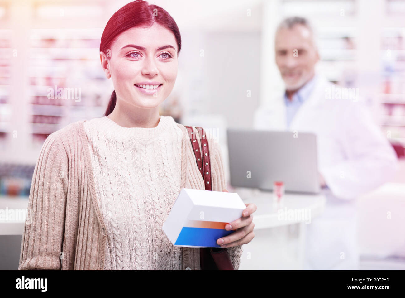 Beaming woman carrying a cure and feeling confident about her health - Stock Image