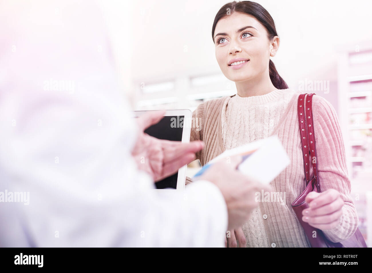 Helpful pharmacist selling a cure to a waiting customer - Stock Image