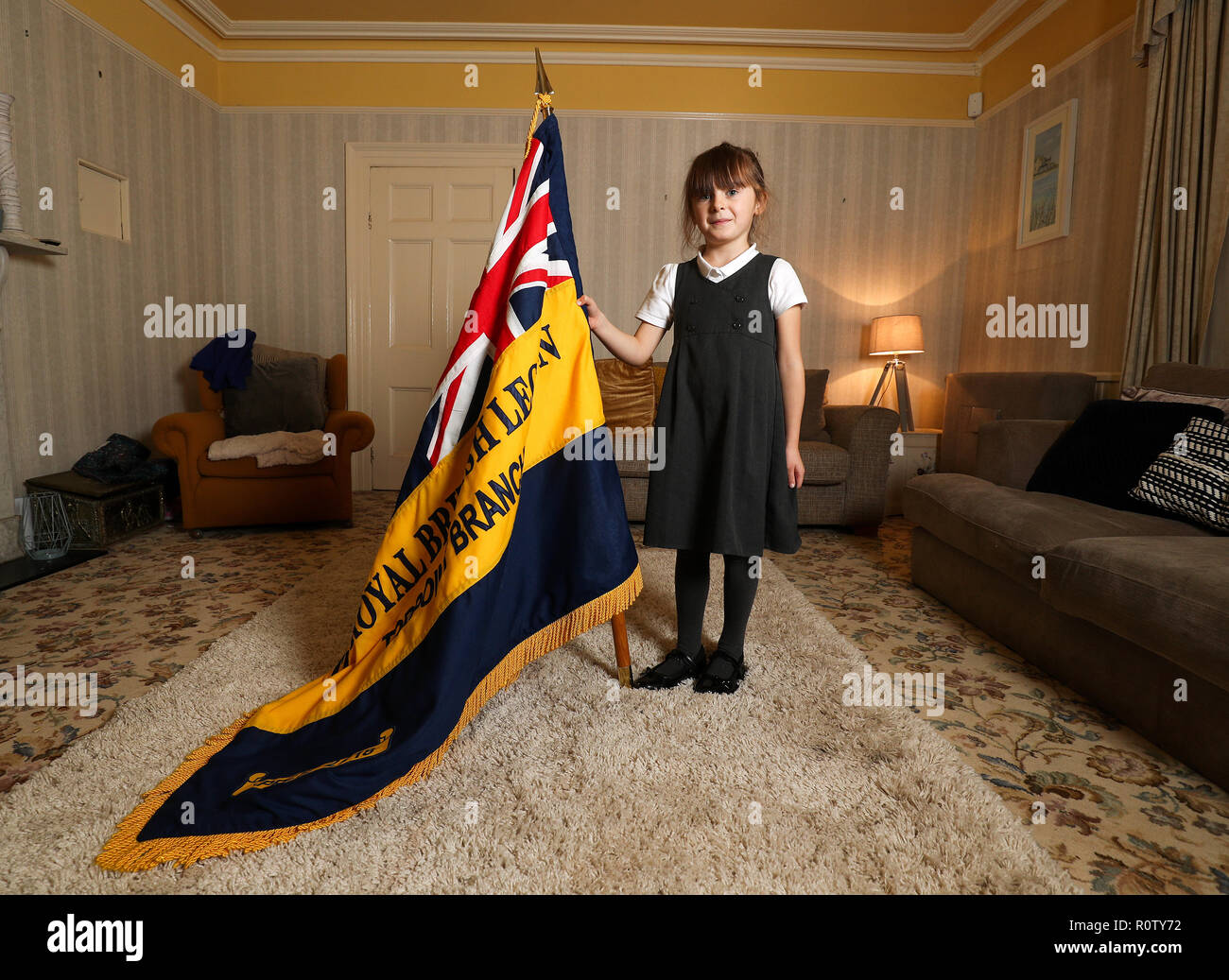 Mollie Stonelake, seven, holds a full-size standard from the Torpoint & District Branch of the Royal British Legion in her family home in Torpoint, Cornwall. Mollie went on her first parade aged five and will carry a specially-made miniature standard in a service on Sunday in her home town of Torpoint in Cornwall. Stock Photo