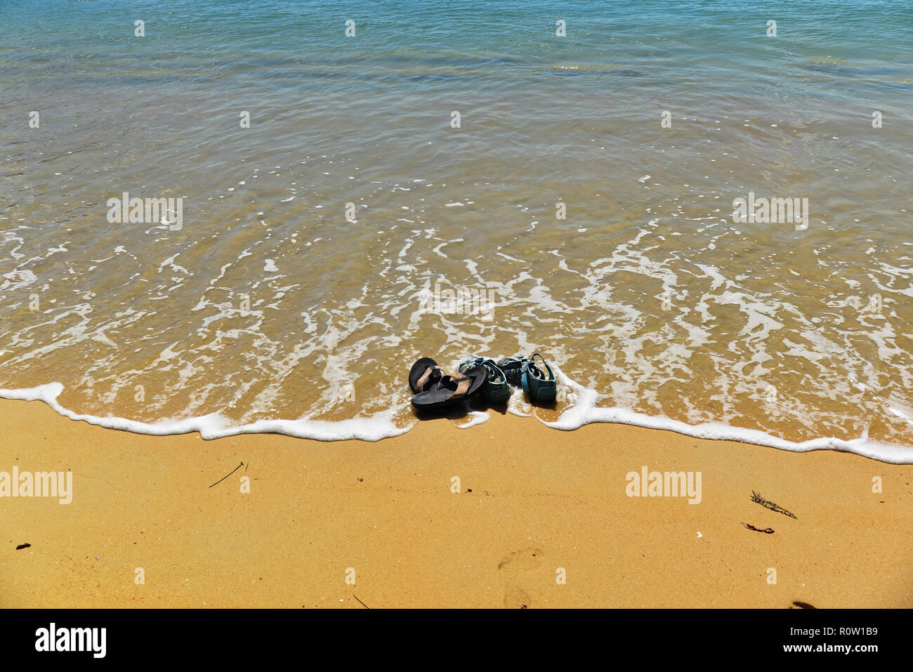 The sea laps over a pair of flip flops and sandals left on a golden beach - Stock Image