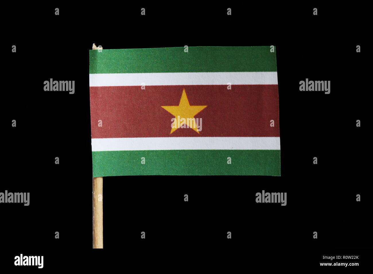 A official flag of Suriname on toothpick on black background. A horizontal triband of green and red with large white border with the large yellow star - Stock Image