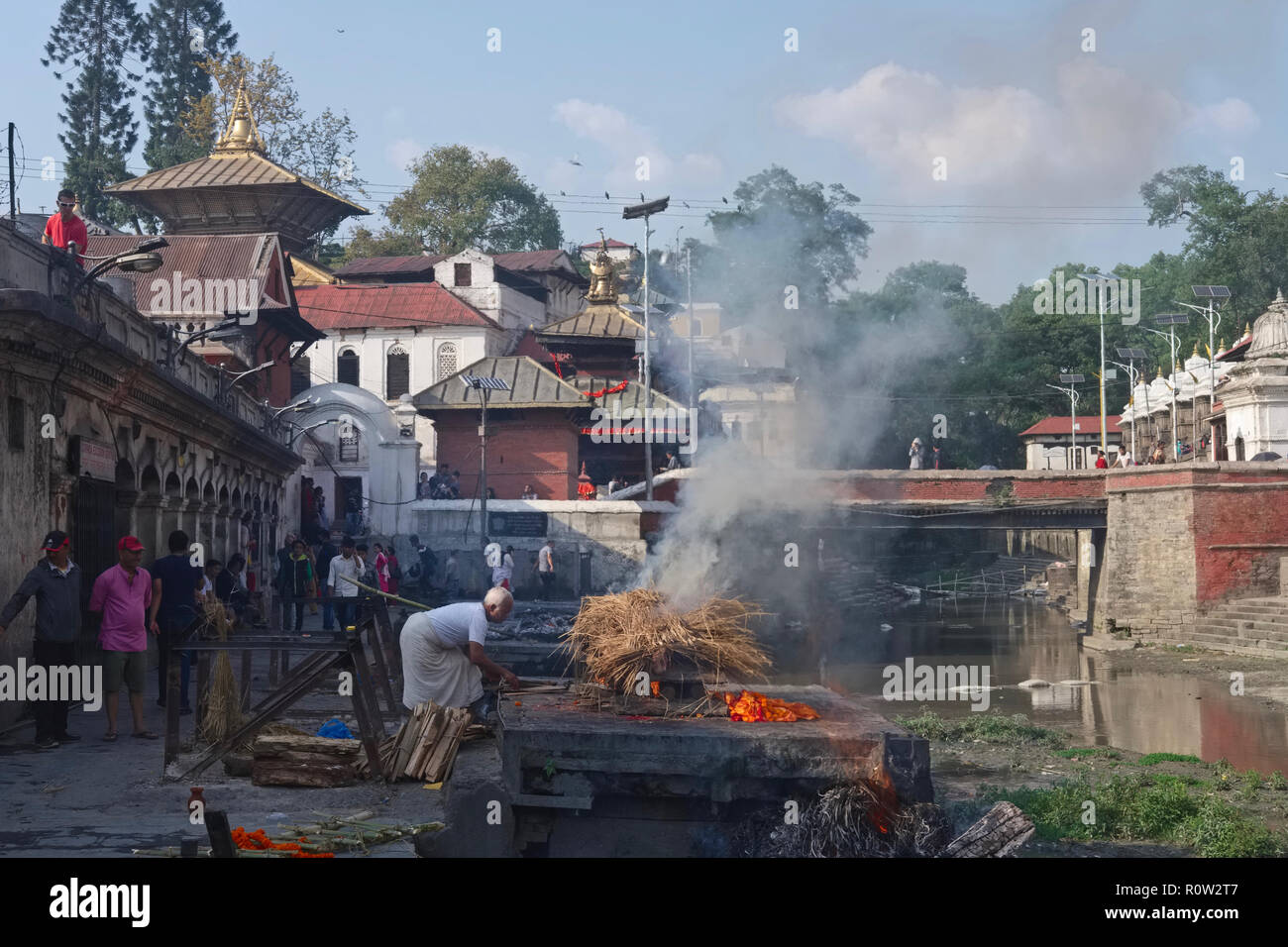 At Pashupatinath Temple by the Bagmati River in Kathmandu, Nepal, along with Hindu rules, a man from the Dom caste conducts the cremation of a Hindu - Stock Image