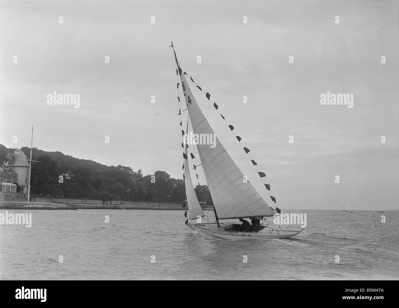 Saling yacht 'Asphodel' (K5) with prize flags, 1922. Creator: Kirk & Sons of Cowes. - Stock Image