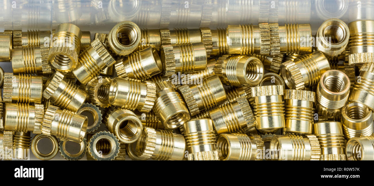 Threaded inserts close-up with mirroring in box. Decorative glossy thread bushings. Pile of small metallic fasteners in golden color. Build, assembly. - Stock Image