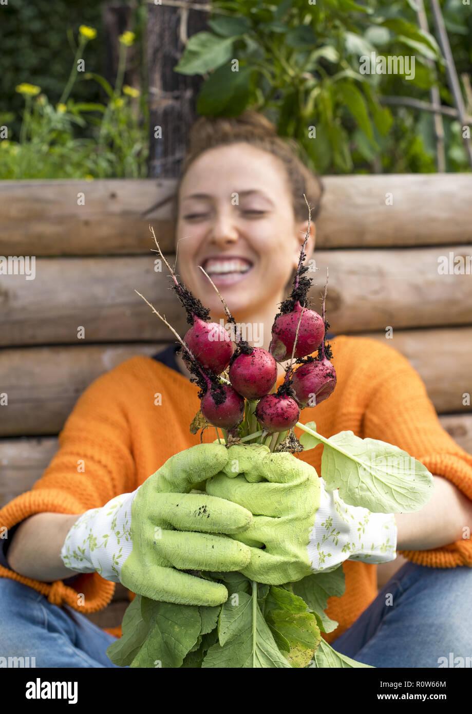 Junge Frau im Garten, erntet Radieschen (model-released) Stock Photo
