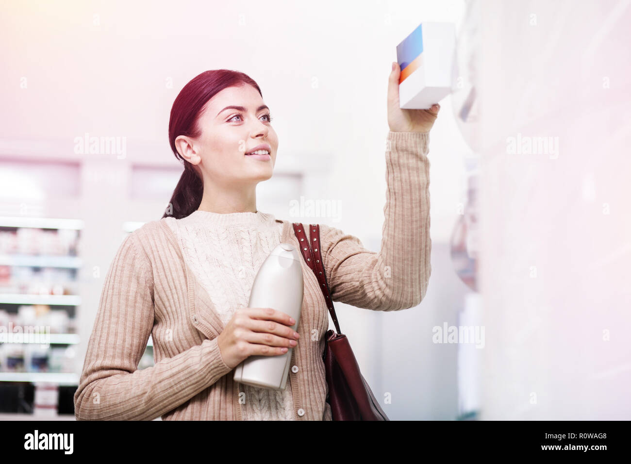 Attractive female customer buying shampoo and pills - Stock Image