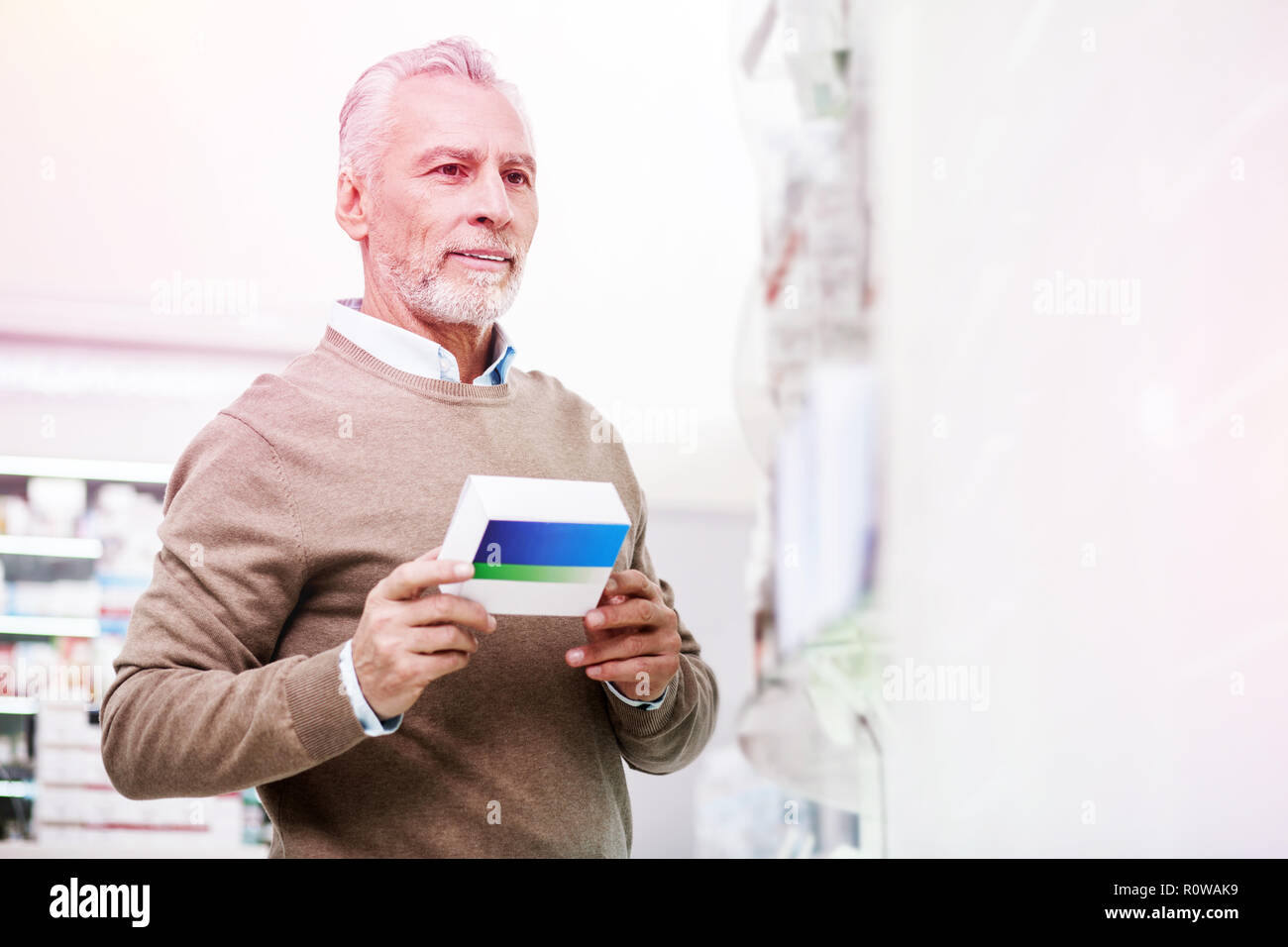 Pondering elder client carrying a package of prescribed pills - Stock Image