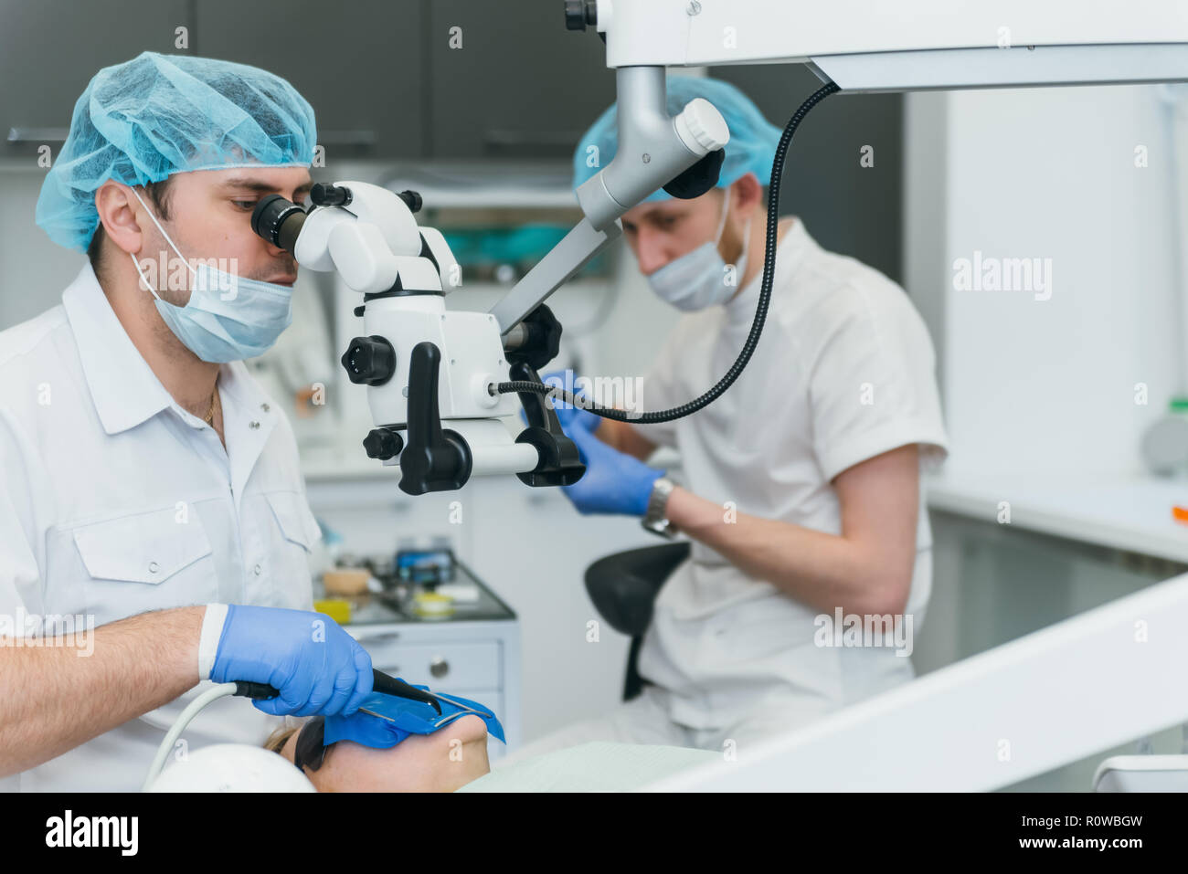 Doctor used microscope. Dentist is treating patient in modern dental office. Operation is carried out using cofferdam. Client is inserted and restored teeth, make denture. - Stock Image