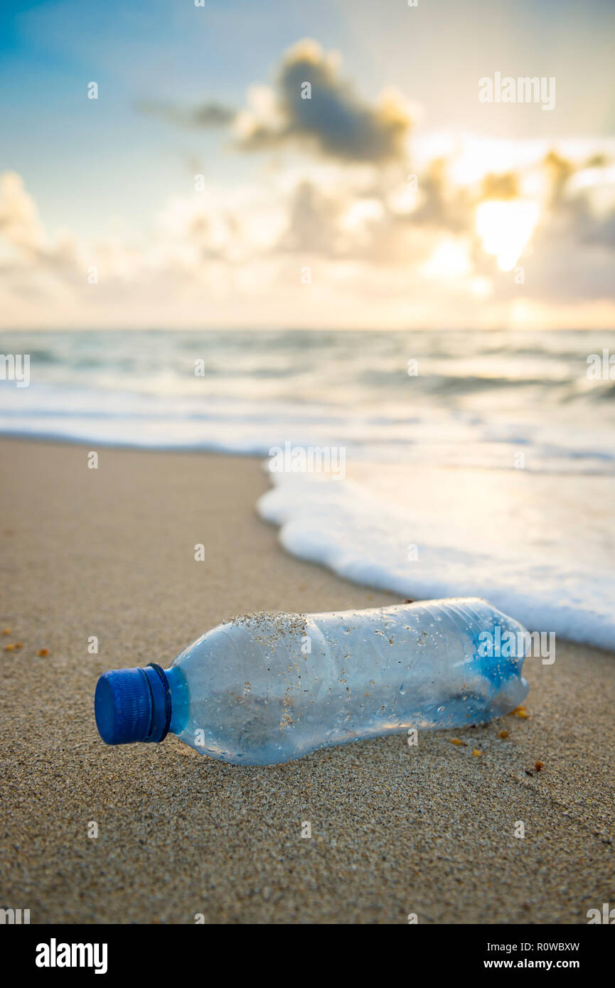 Plastic waste water bottle washed up in the waves on the shore of an empty tropical beach Stock Photo
