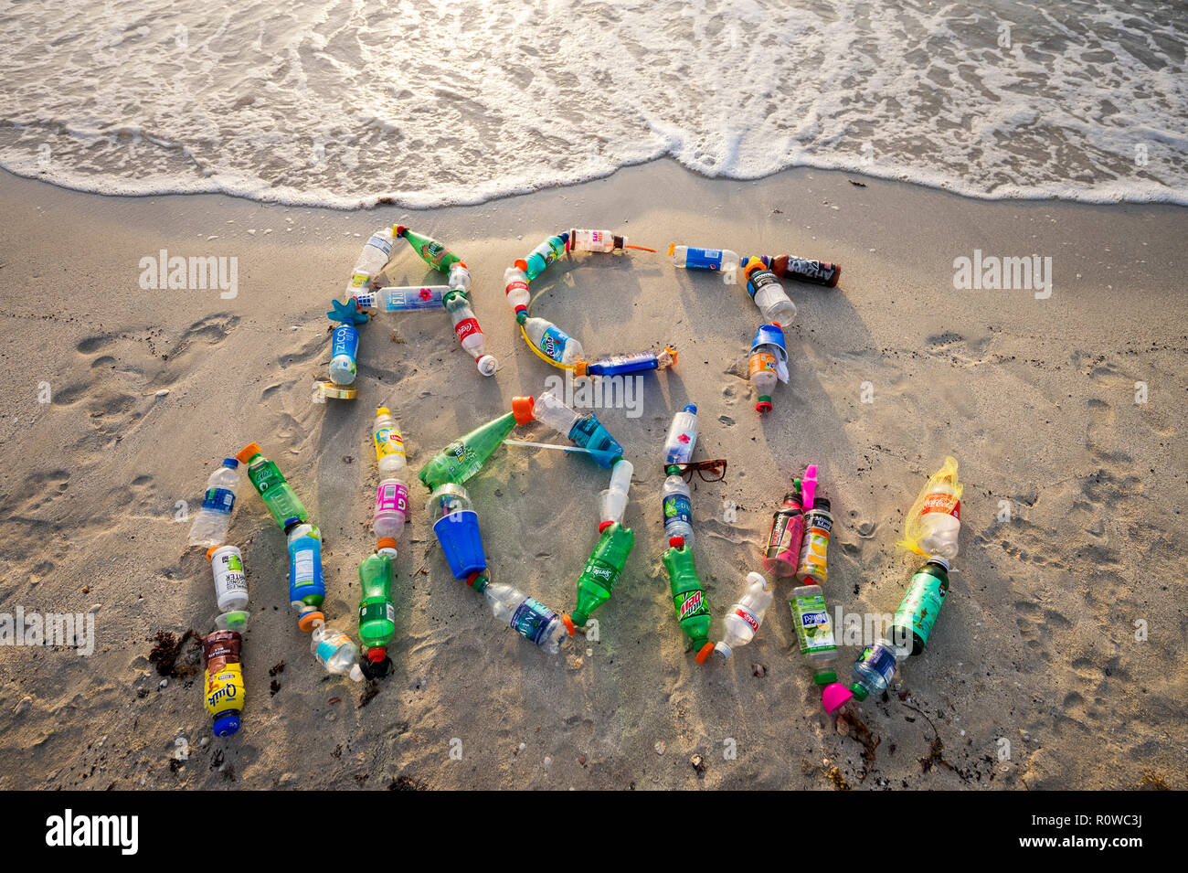 MIAMI - CIRCA AUGUST, 2018: Ocean plastic pollution awareness message spelling out Act Now made from consumer drink bottles found on the beach - Stock Image