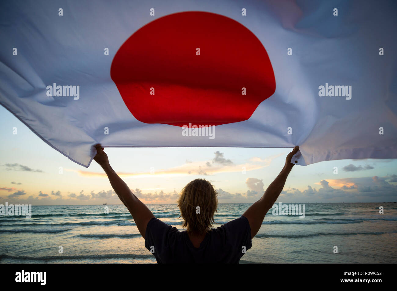 Silhouette of man holding Japanese flag in front of soft sunrise sky at the beach - Stock Image